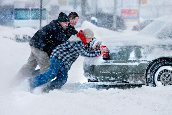 Парни выталкивают машину из снега