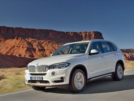 Белый BMW X5 на фоне горы