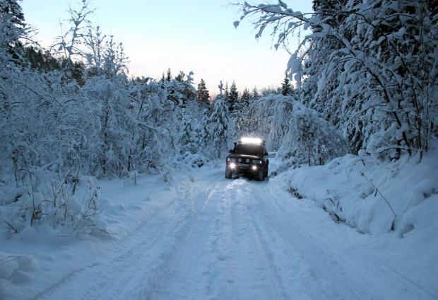 Внедорожник оснащенный люстрой на зимней дороге в лесу