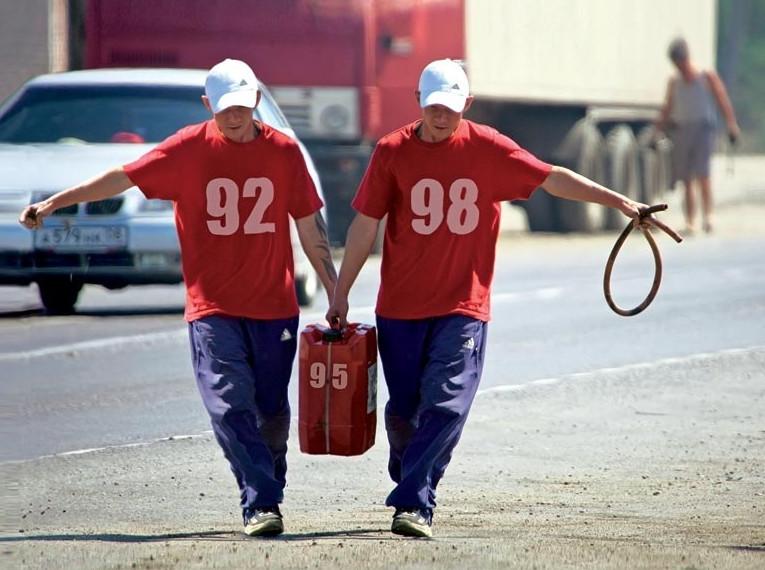 Два рабочих несут канистру бензина