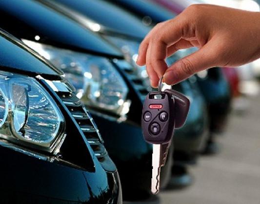 Автомобили капотом вперед и рука с ключами от одного из них